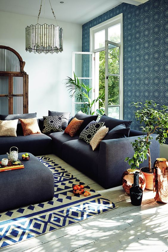 Blue patterned wallpaper with bronze accessories and white floorboards