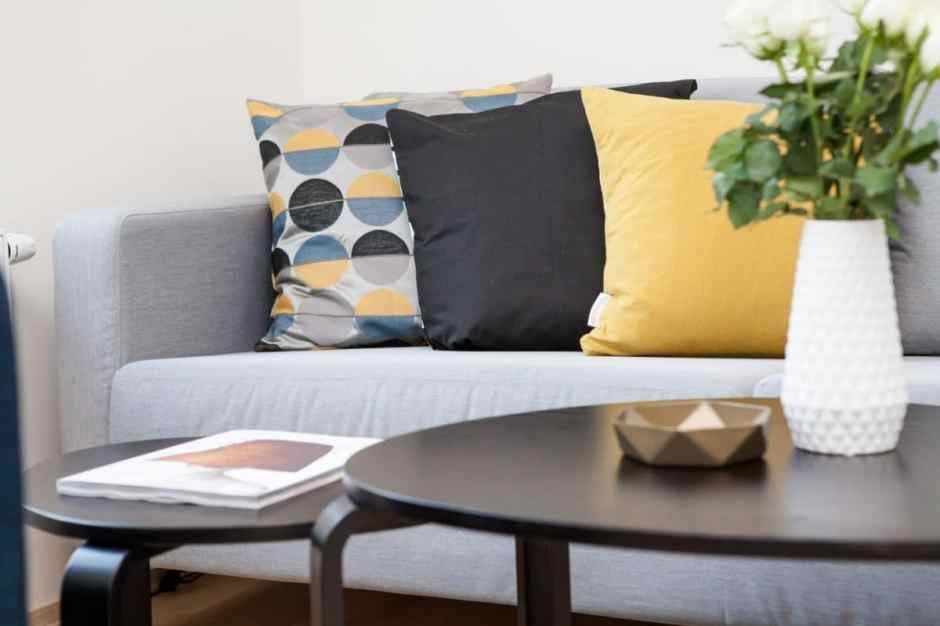 Mustard yellow and grey cushions on a grey sofa