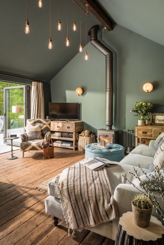 blue grey room with industrial lighting and wood burning stove