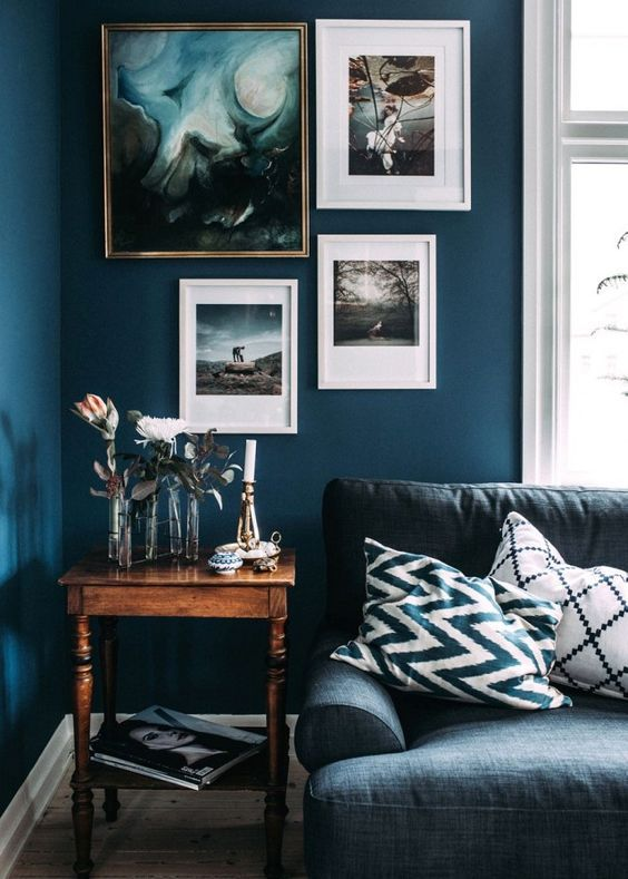 Moody paint colours and blue walls with artwork and grey sofa